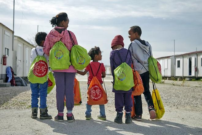 Φωτογραφία που δόθηκε σήμερα στη δημοσιότητα και εικονίζει μαθητές από το 7ο δημοτικό Αγίας Παρασκευής παιδιά προσφύγων στο Κέντρο φιλοξενίας προσφύγων στον Ελαιώνα με τα σακίδια αγάπης που συγκεντρώσαν  μαθητές από τα σχολεία Φιλαδέλφειας - Χαλκηδόνας και Νέας Ιωνίας, την Τετάρτη 2 Μαρτίου 2016. Ένα σακίδιο από τα παιδικά χέρια ενός μαθητή φτάνει στα χέρια ενός προσφυγόπουλου. Γεμάτο με παιχνίδια, χρηστικά αντικείμενα και μηνύματα, άλλοτε για καλό ταξίδι, για ειρήνη, για ελπίδα, για φιλία. Από τον Ιανουάριο του 2016, μαθητές δημοτικών, γυμνασίων και λυκείων της Αττικής κι ένα δημοτικό σχολείο από την ορεινή Αρκαδία, δίνουν απλόχερα αγάπη και προσφέρουν ό,τι μπορεί να είναι χρήσιμο σε ένα παιδί που ζει σε κέντρο φιλοξενίας προσφύγων, Τετάρτη 6 Απριλίου 2016. ΑΠΕ-ΜΠΕ/Αλληλεγγύη για όλους/Γιάννης Ζινδριλής