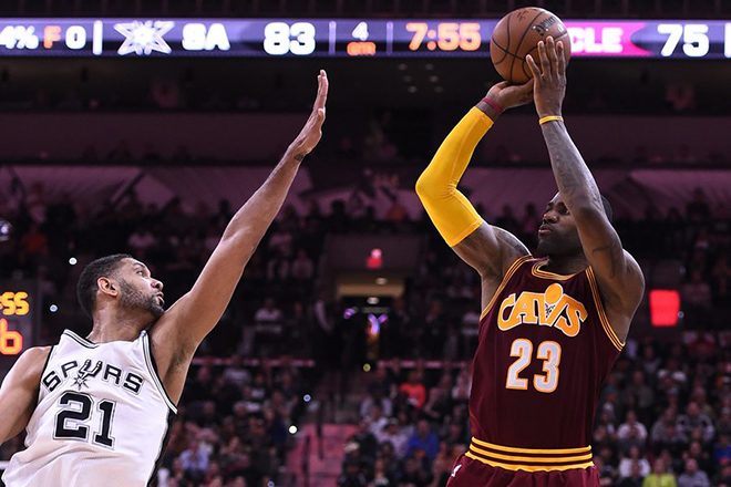 epa05102630 Cleveland Cavaliers player LeBron James (R) takes a shot against San Antonio Spurs player Tim Duncan (L) in the second half of their NBA basketball game at the AT&T Center in San Antonio, Texas, USA, 14 January 2016.  EPA/LARRY W. SMITH CORBIS OUT