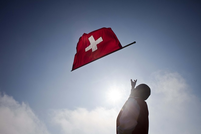 A man throws a Swiss national flag during the opening ceremony of the final day of the Federal Alpine Wrestling Festival (Eidgenoessisches Schwing- und Aelplerfest) in Frauenfeld August 22, 2010. Swiss Alpine wrestling, called 'Schwingen', is the oldest sport in Switzerland. REUTERS/Miro Kuzmanovic (SWITZERLAND - Tags: SPORT SOCIETY) - RTXSBZH