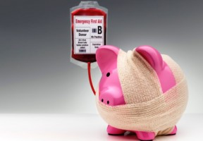 Bandaged pink piggy bank receiving a transfusion
