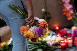epa05438468 A sympathizer adds a bunch to the flowers and candles lying in front Olympia shopping center (OEZ) which was the scene of a shooting spree in Munich,Germany, 23 July 2016. According to authorities, at least 10 people died, including the suspect, and 16 were hospitalized after a shooting spree at the Olympia shopping centre in Munich on 22 July 2016. Police on 23 uly 2016 said it was a 'classical amok run' by an 18-year-old Munich-born young man.  EPA/SVEN HOPPE