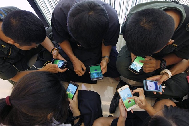 epa05464292 Thai students play 'Pokemon Go' on their smartphones at a shopping mall in Bangkok, Thailand, 08 August 2016. The 'Pokemon Go' game allows smartphone users to use GPS to catch Pokemon characters in their surroundings. The National Broadcasting and Telecommunications Commission (NBTC) is expected to issue 'No Pokemon catching' zone restrictions for places especially at religious and historic sites such as the Royal Palace, Buddhist temples, important government offices and places that hold up national security as well as hospitals and private areas. The NBTC also expressed concern to 'Pokemon Go' players about unexpected mobile phone costs and possible accidents while playing the game.  EPA/RUNGROJ YONGRIT