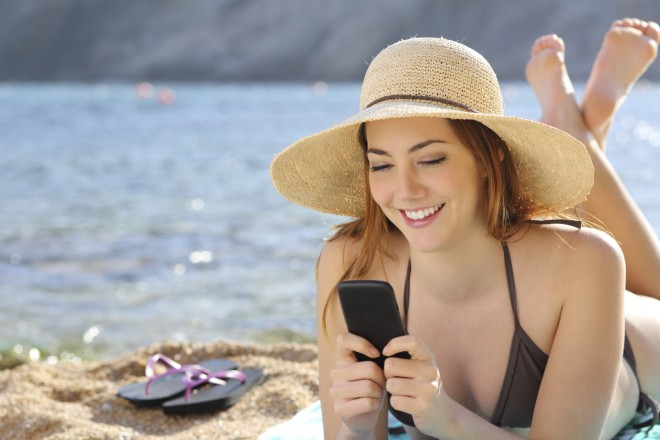 Woman on the beach texting a smart phone in summer with the sea in the background