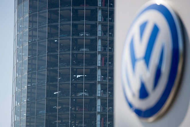 epa05498938 A VW logo can be seen on in front of a tower containing new cars at the Volkswagen factory in Wolfsburg, Germany, 19 August 2016. Volkswagen (VW) has been forced to temporarily shut down its production of popular 'Golf' model in Wolfsburg and the 'Passat' model in Emden due to suppliers that have stopped delivery of car parts to the VW factories.  EPA/SEBASTIAN GOLLNOW