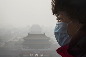 BEIJING, CHINA - NOVEMBER 15: A Chinese woman wears a mask as haze from smog caused by air pollution hangs over the Forbidden City on November 15, 2015 in Beijing, China. As a result of industry, the use of coal, and automobile emissions, the air quality in China's capital and other major cities is often many times worse than standards set by the World Health Organization. (Photo by Kevin Frayer/Getty Images)