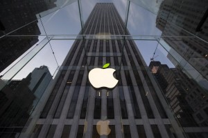 The leaf on the Apple symbol is tinted green at the Apple flagship store on 5th Avenue in New York, in this file picture taken April 22, 2014. Through bursting bubbles and crashing markets, revenue and profit at America's top companies have expanded smartly over the past 18 years -- nearly tripling in the case of operating income. A Reuters analysis of revenue, operating profit and head count growth at the 100 largest non-bank companies between 1995 and 2013 documents a steady divergence between their ability to generate earnings and the need to hire employees. To match Insight USA-ECONOMY/EMPLOYMENT    REUTERS/Brendan McDermid/Files  (UNITED STATES - Tags: ENVIRONMENT SCIENCE TECHNOLOGY BUSINESS)