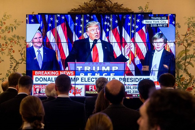 epa05623747 People look at a screen with a transmission of US Republican presidential nominee Donald Trump as he delivers a speech on stage at Trump's 2016 US presidential Election Night event as votes continue to be counted at the New York Hilton Midtown in New York, during an election party at the US embassy in Brussels, Belgium, 09 November 2016. US businessman Republican Donald Trump has won the US presidential election.  EPA/STEPHANIE LECOCQ