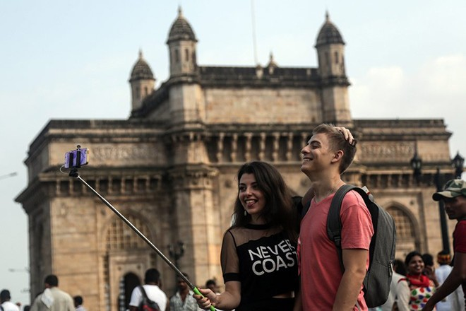 epa05556427 A picture made available on 26 September 2016 shows foreign tourists taking a selfie in front of the Gateway of India, one of the famous tourist spot in Mumbai, India, 25 September 2016. United Nations World Tourism Day celebrations will be observed on 27 September 2016.  EPA/DIVYAKANT SOLANKI