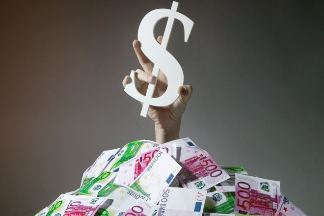 GERMANY - JANUARY 07: Feature: the Dollar is inundatet with Euros / price gains of the Euro against the Dollar, Hand with a Dollar sign coming out of a pile of Euro notes. (Photo by Ulrich Baumgarten via Getty Images)