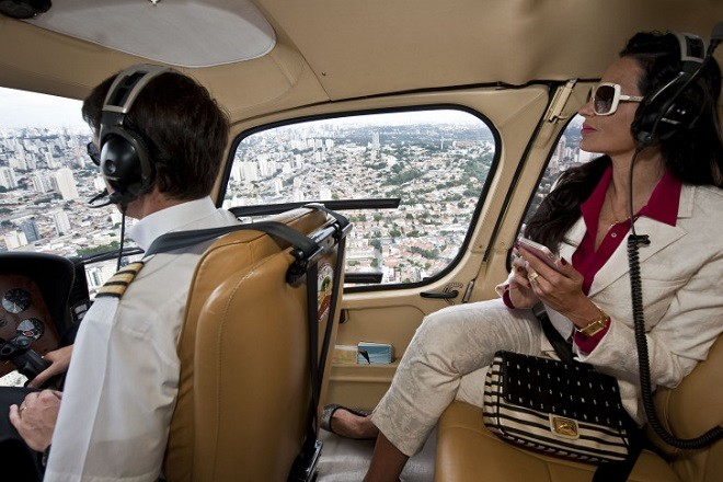 Brazilian millionaire Cozete Gomes (R) checks her cellphone as she flies on her helicopter over Sao Paulo, on April 4, 2013. Cozete Gomes owns eight companies in the sector of promotional events, assignment of temporary labor, outsourcing of labor and services, recruitment and selection, training and events, which last year grossed about 100 million reais (US dollars 50,3 millions).      AFP PHOTO / Nelson ALMEIDA        (Photo credit should read NELSON ALMEIDA/AFP/Getty Images)
