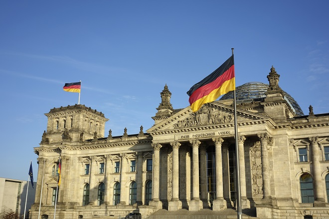 Frontal view of Reichstag building with German flag waving in a beautiful day with blue sky, Berlin, Germany, Europe.