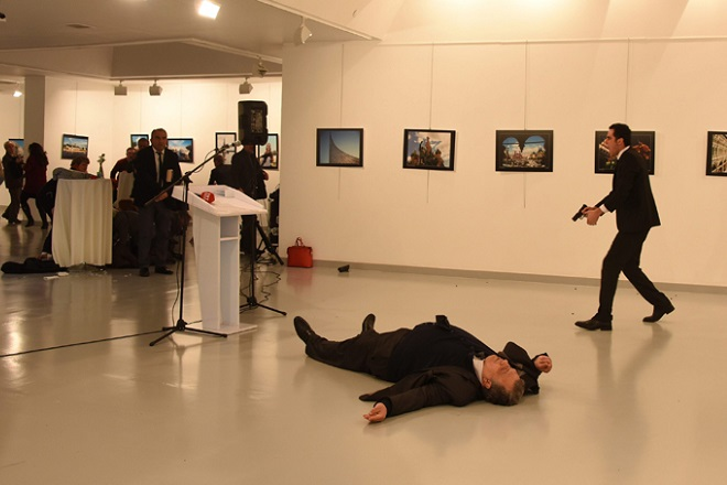 epa05682748 Gunman (R) clutching a pistol stands near slain Russia's ambassador to Turkey, Andrey Karlov's body (down), after he shot him during an art exhibition in Ankara, Turkey, 19 December 2016. Russia's ambassador to Turkey, Andrey Karlov, has been shot at an art exhibition in the Turkish capital of Ankara. Karlov has died of his wounds after the attack, Russia's Ministry of Foreign Affairs confirmed.  EPA/SOZCU NEWSPAPER VIA DEPO PHOTOS TURKEY OUT