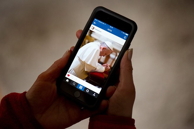 epa05220431 A woman holds a smartphone that shows the Instagram account of Pope Francis, in Dresden, Germany, 19 March 2016. The pope starts sharing pictures and short videos with users all over the world using the account name 'Franciscus', the latin version of his name.  EPA/ARNO BURGI
