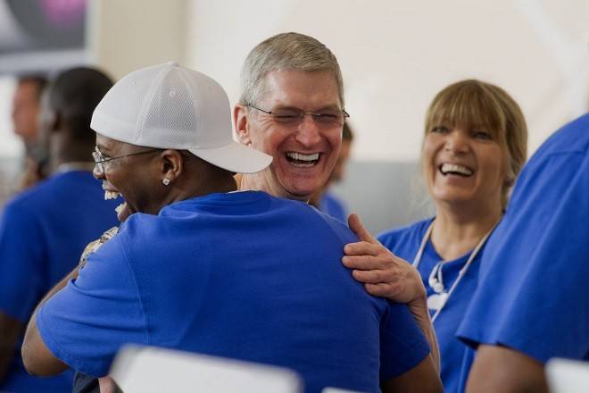 Tim Cook, chief executive officer of Apple Inc., center, hugs an employee during the sales launch for the iPhone 6 and iPhone 6 Plus at the Apple Inc. store in Palo Alto, California, U.S., on Friday, Sept. 19, 2014. Apple Inc.'s stores attracted long lines of shoppers for the debut of the latest iPhones, indicating healthy demand for the bigger-screen smartphones. The larger iPhone 6 Plus is already selling out at some stores across the U.S. Photographer: David Paul Morris/Bloomberg via Getty Images