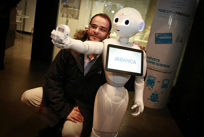 epa05675286 A man poses for a selfie with R4, installed in a Japanese humanoid robot called 'Pepper', at an office of Abanca in A Coruna, Spain, 14 December 2016. R4, who's software has been designed by the bank, is meant to help with commercial tasks in the office.  EPA/CABALAR