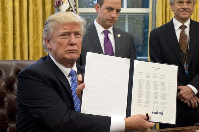 "epa05744777 US President Donald J. Trump shows the Executive Order withdrawing the US from the Trans-Pacific Partnership (TPP) after signing it in the Oval Office of the White House in Washington, DC, USA, 23 January 2017. They concerned the withdrawal of the United States from the Trans-Pacific Partnership (TPP), a US Government hiring freeze for all departments but the military, and ""Mexico City"" which bans federal funding of abortions overseas.  EPA/Ron Sachs / POOL"