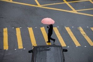 epa05591670 A man protects himself with an umbrella while crossing a street during a heavy rain in Hong Kong, China, 19 October 2016. Hong Kong Observatory issued a black rainstorm warning for the territory amid northeast monsoon. More unstable weather is predicted as as super typhoon Haima heads directly towards the city, possibly skirting within 100 kilometers of the city on 21 October.  EPA/JEROME FAVRE