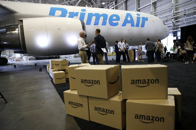 "Amazon.com boxes are shown stacked near a Boeing 767 Amazon ""Prime Air"" cargo plane on display Thursday, Aug. 4, 2016, in a Boeing hangar in Seattle. Amazon unveiled its first branded cargo plane Thursday, one of 40 jetliners that will make up Amazon's own air transportation network of 40 Boeing jets leased from Atlas Air Worldwide Holdings and Air Transport Services Group Inc., which will operate the air cargo network. (AP Photo/Ted S. Warren)"
