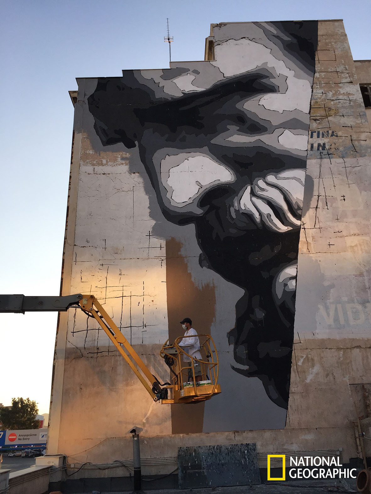 ATHENS - The street artist INO works on a massive mural of the ancient Greek thinker Democritus.(photo credit:  NGT/Chris Dye)