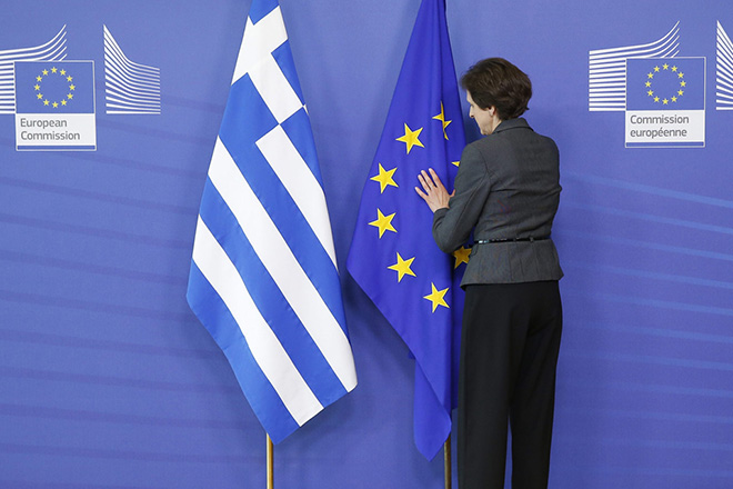 epa04782029 A woman of the protocoll arranges a Greek (L) and EU flag at the EU commission headquarters in Brussels, Belgium, 03 June 2015. Greek Prime Minister Alexis Tsipras meets European Commission President Jean-Claude Juncker in Brussels amid intense media speculation in Athens that a breakthrough is imminent in the country's bailout saga. The head of the Eurogroup of finance ministers, Jeroen Dijsselbloem is also set to join the meeting, underlining hopes that a compromise deal between Athens and its international creditors is taking shape.  EPA/JULIEN WARNAND