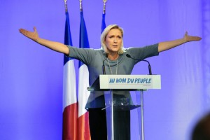 """TOPSHOT - French far-right Front National (FN) party's President, Marine Le Pen, gestures as she delivers a speech on stage during the FN's summer congress in Frejus, southern France, on September 18, 2016.  Marine Le Pen's slogan reading """"In the name of the [French] people"""" is seen on the rostrum. / AFP / Franck PENNANT        (Photo credit should read FRANCK PENNANT/AFP/Getty Images)"""