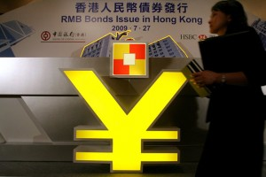 epa01807959 A woman walks past a sign of China Yuan Renminbi (RMB) during the launch ceremony of China Development Bank Renminbi-denominated Bonds issued in Hong Kong, China, 27 July 2009. The bonds are offered to both institutional and retail investors, which denomination of RMB 10,000 (1,026 euro) with a tenor of two year.  EPA/YM YIK  EPA