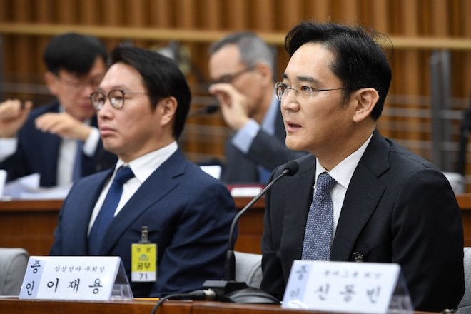 Samsung Group's heir-apparent Lee Jae-Yong (R) answers a question as SK Group chairman Chey Tae-Won (L) listens to during a parliamentary probe into a scandal engulfing President Park Geun-Hye at the National Assembly in Seoul on December 6, 2016.  The publicity-shy heads of South Korea's largest conglomerates faced their worst nightmare on December 6, as they were publicly grilled about possible corrupt practises before an audience of millions. / AFP PHOTO / POOL / JUNG YEON-JE