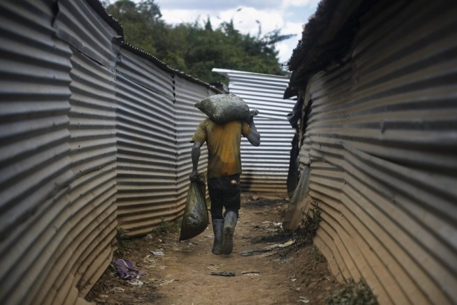 epa05202292 (27/28) A miner carries sacks filled with gold-containing ores that he and others extracted from the mine at a gold mining site in Osiri, Migori county, western Kenya, 01 March 2016. The recent explorations conducted by the government and private companies are said to have revealed large gold deposits in western Kenya, which could lead to the large-scale commercial mining that could put Kenya on the map of the top gold producers in Africa.  EPA/DAI KUROKAWA PLEASE REFER TO ADVISORY NOTICE (epa05202265) FOR FULL PACKAGE TEXT
