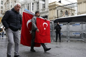 epa05845817 A man carrying Turkish flags walks past a Turkish armed riot policeman in front of the Dutch Consulate in Istanbul, Turkey, 13 March 2017. Turkish Family Minister Fatma Betul Sayan Kaya was barred by Dutch police from entering the Turkish consulate in Rotterdam on 11 March, after the Dutch government had denied landing rights to Turkish Foreign Minister Cavusoglu who planned a speech at the consul's residence in Rotterdam. The incidents have led to a diplomatic row between the two countries, and protests by Turkish citizens in the Netherlands as well as in Turkey.  EPA/SEDAT SUNA