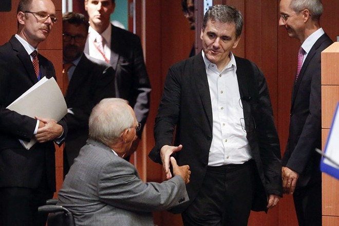 epa04883374 Greek Finance minister Euclid Tsakalotos (R) and German Finance Minister Wolfgang Schaeuble (L) shake hands at the start of a special Eurogroup Finance ministers meeting, on the Greek crisis, at the European Council headquarters in Brussels, Belgium, 14 August 2015. Greeks members of Parliament have approved on 14 August the third bailout agreement in five years with European Union.  EPA/OLIVIER HOSLET