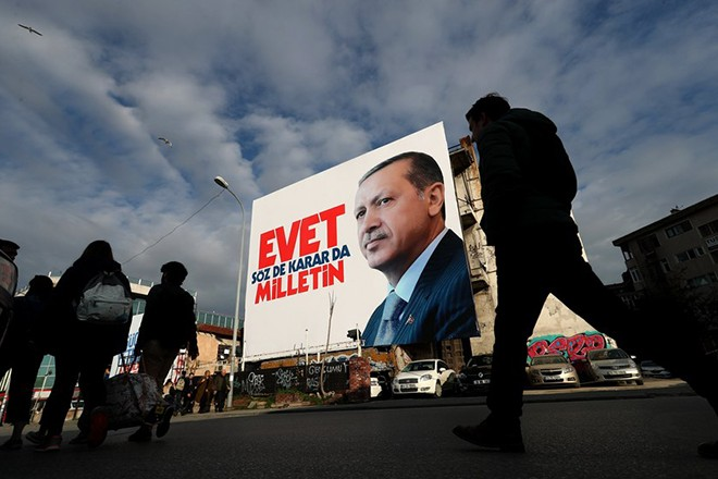 epaselect epa05860181 Turkish people walk in front of a giant picture of Turkish President Recep Tayyip Erdogan reading, 'Vote Yes, only public can speak and make decision', in Istanbul, Turkey, 20 March 2017. The Turkish parliament on 21 January approved a reform of the constitution to change the country's parliamentarian system of governance into a presidential one, which the opposition denounced as giving more power to Turkish president Recep Tayyip Erdogan. A referendum on the amendments is expected to be held in April.  EPA/SEDAT SUNA
