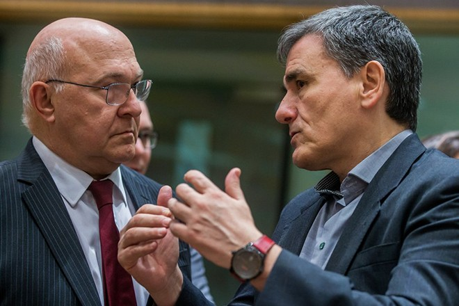 epa05860144 French Finance Minister Michel Sapin (L), Greek Finance Minister Euclid Tsakalotos (R) speaking prior to the start of a Eurogroup Finance Ministers' meeting at the European Council headquarters in Brussels, Belgium, 20 March 2017.  EPA/STEPHANIE LECOCQ