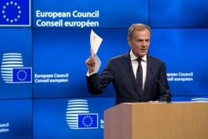 European Council President Donald Tusk holds up the document from the UK during a media conference at the Europa building in Brussels on Wednesday, March 29, 2017. Tusk has received a letter from British Prime Minister Theresa May, invoking Article 50 of the bloc's key treaty, the formal start of exit negotiations. (AP Photo/Virginia Mayo)