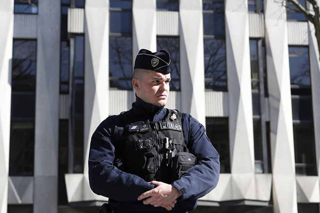 epa05851900 A Police officer with stands guard outside the International Monetary Fund (IMF) headquarters in Paris, France, 16 March 2017. An employee of the IMF has been injured in the face after an explosion while opening a letter.  EPA/IAN LANGSDON
