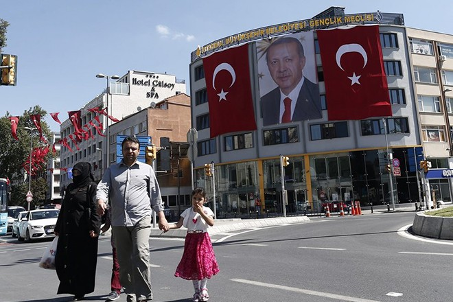 epa05435062 Tourists walk in front of the picture of Turkish President Recep Tayyip Erdogan, in Istanbul, Turkey, 21 July 2016. Turkish President Recep Tayyip Erdogan has declared a three-month state of emergency and caused the dismissal of 50,000 workers and the arrest of 8,000 people after the 15 July failed coup attempt. At least 290 people were killed and almost 1,500 injured amid violent clashes on 15 July as certain military factions attempted to stage a coup d'etat. The UN and various governments and organizations have urged Turkey to uphold the rule of law and to defend human rights.  EPA/SEDAT SUNA