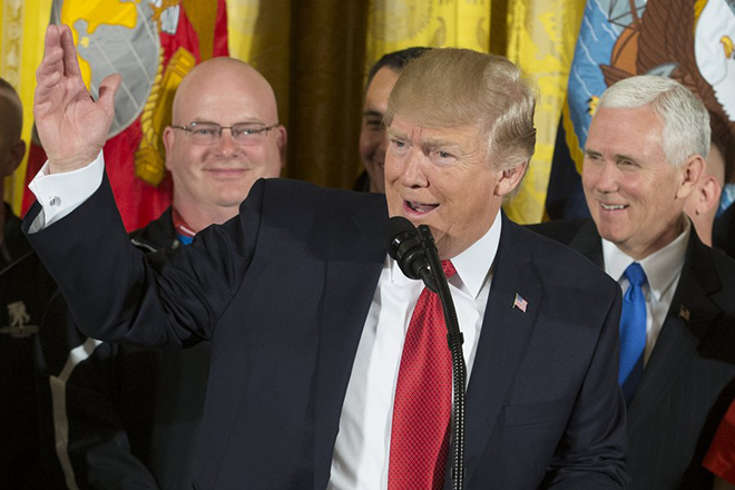 epa05892307 US President Donald J. Trump (Front) delivers remarks beside US Vice President Mike Pence (Back R) and veterans at an event hosting participants of the Wounded Warrior Project Soldier Ride, in the East Room of the White House in Washington, DC, USA, 06 April 2017. A cycling event to help Wounded Warriors restore their physical and emotional well-being, the Soldier Ride also raises awareness of US veterans who battle the physical and psychological damages of war.  EPA/MICHAEL REYNOLDS