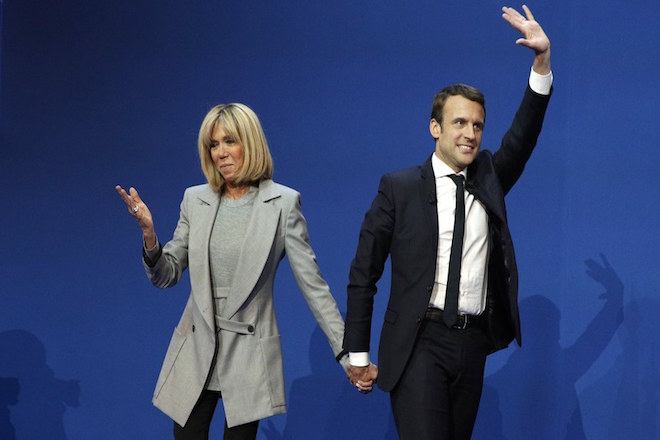 epa05924539 French presidential election candidate for the 'En Marche!' (Onwards!) political movement, Emmanuel Macron (R) celebrates with his wife Brigitte Trogneux (L) after the first round of the French presidential elections in Paris, France, 23 April 2017. Media reports that polling agencies projections place Macron and far-right Front National (FN) party candidate Marine Le-Pen in the lead positions for the vote. France will hold the second round of the presidential elections on 07 May 2017.  EPA/YOAN VALAT
