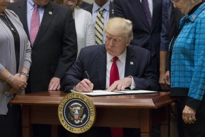 epa05929504 US President Donald J. Trump (C) signs the 'Education Federalism Executive Order' in the Roosevelt Room of the White House in Washington, DC, USA, 26 April 2017. The executive order will launch a review of regulations for school districts, directing the Department of Education to change measures that the Trump administration has judged are examples of the federal government over-extending its authority.  EPA/MICHAEL REYNOLDS