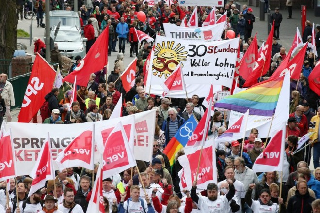epa04728207 People rally with flags and banners during a demonstration organized by the Confederation of German Trade Unions (DGB) on May Day in Hamburg,Germany, 01 May 2015. This year's DGB rally takes place under the motto 'We design the future of labour'.  EPA/BODO MARKS
