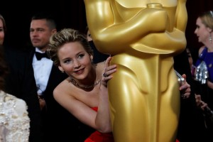 "Jennifer Lawrence, best supporting actress nominee for her role in the film ""American Hustle"", peeks around an Oscar statue on the red carpet as actor Brad Pitt (L) looks on at the 86th Academy Awards in Hollywood, California March 2, 2014. REUTERS/Adrees Latif (UNITED STATES  - Tags: ENTERTAINMENT)(OSCARS-ARRIVALS) - RTR3FYAG"