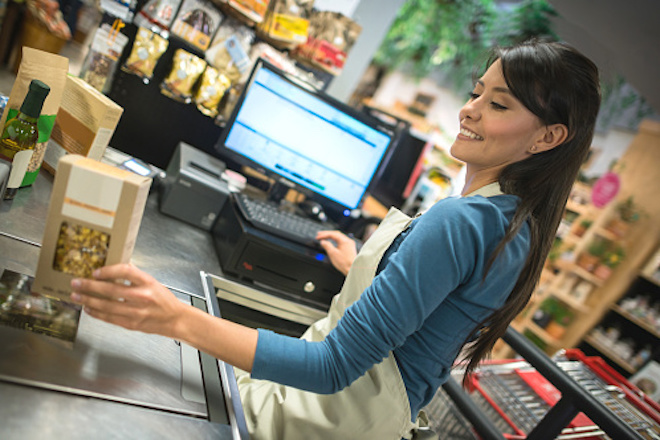 Latin cashier working at a supermarket