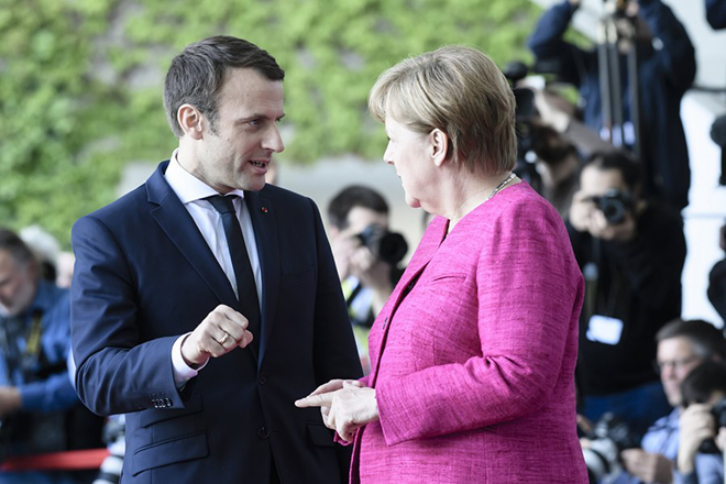 epa05966571 German Chancellor Angela Merkel (R) and newly elected French President Emmanuel Macron (L) talk on his arrival at the German Chancellery in Berlin, Germany, 15 May 2017. The French President makes his inaugural foreign visit to Germany.  EPA/CLEMENS BILAN
