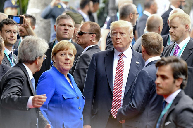 epa05991274 Italian Prime Minister Paolo Gentiloni (R) asks German Chnacellor Angela Merkel (2-L) and US President Donald J. Trump (3-R) to join a walk off after the group photocall at on the first day of the G7 Summit, in Taormina, Italy, 26 May 2017. Others are not identified. Heads of States and of Governments of the G7, the group of most industrialized economies, plus the European Union, meet in Taormina, Italy, from 26 to 27 May 2017 for a summit titlked 'Building the Foundations of Renewed Trust' which is aimed at discussing 'citizen safety, economic, environmental and social sustainability and the reduction of inequalities' as well as 'innovation, skills and labor in the age of the Next Production Revolution', the Italian G7 Presidency said in a media release.  EPA/CIRO FUSCO  EPA/CIRO FUSCO