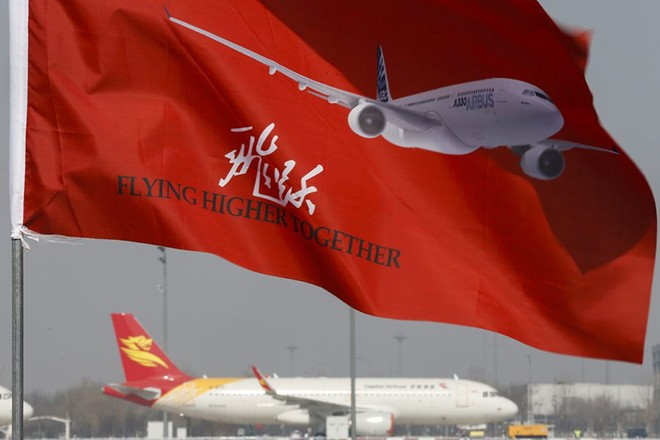 epa05189869 An Airbus slogan is printed on a flag as an aircraft is seen at a distance, during ground-breaking ceremonies for an Airbus A330 Completion and Delivery Center at Airbus Tianjin facilities in Tianjin municipality, China, 02 March 2016. The facility will be installing cabins and furnishing, and conduct exterior painting in Airbus aircraft coming from its assembly line in France.  EPA/ROLEX DELA PENA