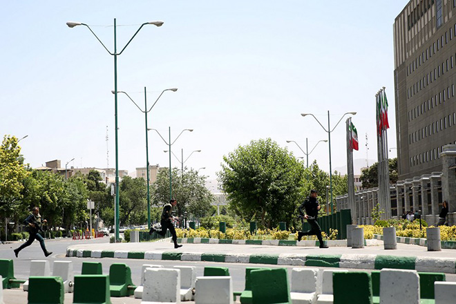 epa06014191 Iranian policemen run around the parliament building during an attack in Tehran, Iran, 07 June 2017. At least seven people were killed and several others were wounded following twin attacks on Iran's parliament building and the mausoleum of former supreme leader, Ayatollah Khomeini, in the Iranian capital Tehran on 07 June, according to official sources.  EPA/ALI KHARA