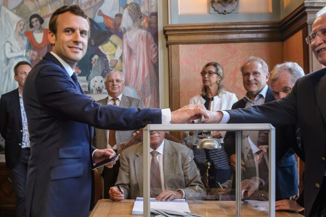 epa06022259 French President Emmanuel Macron (L) casts his ballot at his polling station in the first round of the French legislatives elections in Le Touquet, northern France, 11 June 2017. France holds the first round of parliamentary elections on 11 June 2017, just under two months after Macron took office as French President.  EPA/CHRISTOPHE PETIT TESSON / POOL