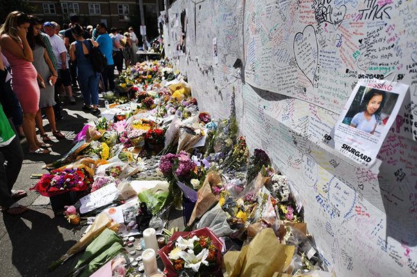 epa06033531 Floral tributes close to Grenfell Tower, a 24-storey apartment block in North Kensington, London, Britain, 17 June 2017. Search and Rescue efforts are continuing to sift through the burnt out remains of the tower. At least 58 people are now missing and presumed dead in the Grenfell Tower disaster, police have said. This latest figure includes the 30 already confirmed to have died in the fire.The cause of the fire is yet not known.  EPA/ANDY RAIN