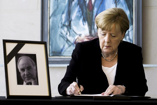 epa06035380 German Chancellor and Chairman of the Christian Democratic Party (CDU), Angela Merkel signs the book of condolence in front of a picture of former German Chancellor Helmut Kohl in Berlin, Germany, 18 June 2017. Kohl was the sixth Federal Chancellor of the Federal Republic of Germany from 1982 to 1998. Kohl has died at the age of 87 in his home in Ludwigshafen on 16 June 2017.  EPA/CARSTEN KOALL