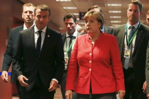 epa06045662 French President Emmanuel Macron (L) and German Chancellor Angela Merkel (R) are on their way to brief the media at the end of the European Council in Brussels, Belgium, 23 June 2017. European heads of states and governments gathered for a two-days European Council meeting on 22 and 23 June mainly focussed 'on the ongoing efforts to strengthen the European Union and protect its citizens through the work on counterterrorism, security and defence, external borders, illegal migration and economic development'. On the meeting's second day the EU leaders were expected 'to reaffirm their commitment to a rules-based multilateral trading system, as well as to free trade and investment', the European Council said in a press release.  EPA/OLIVIER HOSLET