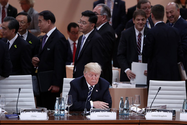 epaselect epa06072834 US President Donald J. Trump (C) sits alone at the beginning of the plenary session of the G20 summit in Hamburg, Germany, 07 July 2017. The G20 Summit (or G-20 or Group of Twenty) is an international forum for governments from 20 major economies. The summit is taking place in Hamburg 07 to 08 July 2017.  EPA/FELIPE TRUEBA